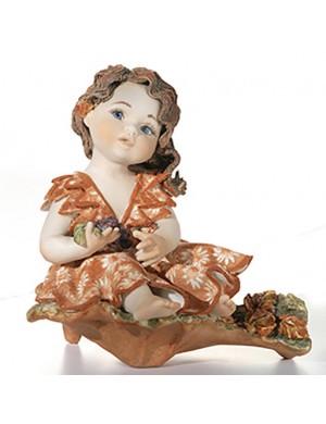 Sibania Autunno  figura in porcellana bimba su base con uva collezione quattro stagioni.