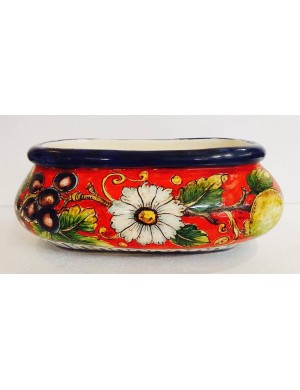 Table decoration in red and blue ceramic flower vase with daisies and fruits